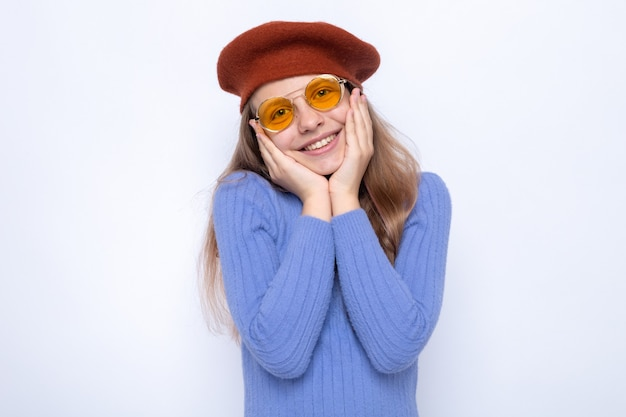 Glimlachend handen op de wangen leggend mooi klein meisje dat een bril met hoed draagt