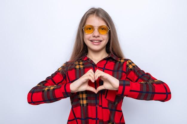 Glimlachend hart gebaar mooi meisje met rood shirt en bril geïsoleerd op een witte muur