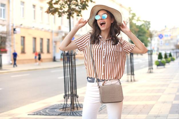 Glimlachend hipster trendy meisje poseren in de zomerstraat van de stad, met hoed.