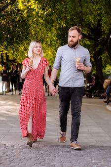 Glimlachend hipsterspaar dat ijs eet en pret in de stad heeft. stijlvolle jonge man met baard en blonde vrouw in rode jurk lopen in de straat.