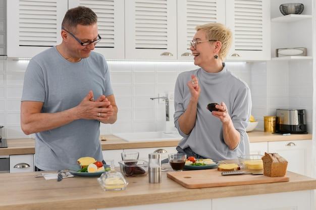 Glimlachend hoger paar dat gezond voedsel met gezonde verse groenten op keuken kookt
