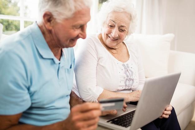 Glimlachend hoger paar dat laptop thuis met behulp van