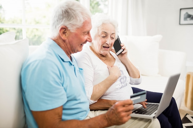 Glimlachend hoger paar die laptop en smartphone thuis gebruiken