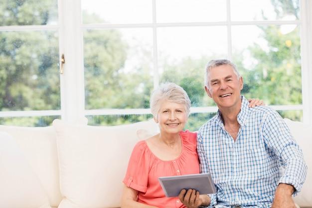 Glimlachend hoger paar die tablet op de bank gebruiken