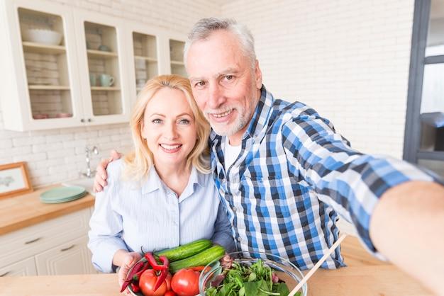 Glimlachend hoger paar die zelfportret met groenten en saladekom nemen in de keuken