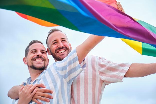 Glimlachend homoseksueel mannelijk paar dat met een regenboogvlag zwaait