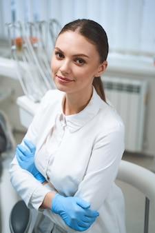 Glimlachend is ze tandarts in medisch uniform en steriele handschoenen terwijl ze geniet van haar werkdag in een modern kantoor