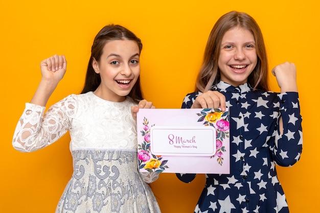 Glimlachend ja gebaar tonen twee kleine meisjes op gelukkige vrouwendag met ansichtkaart geïsoleerd op oranje muur