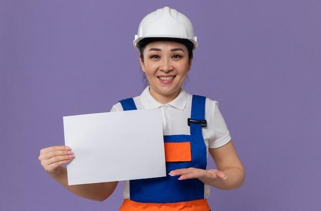 Glimlachend jong aziatisch bouwersmeisje met witte veiligheidshelm die vel papier vasthoudt