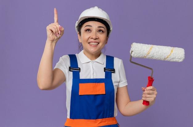 Glimlachend jong aziatisch bouwersmeisje met witte veiligheidshelm die verfroller vasthoudt en omhoog wijst
