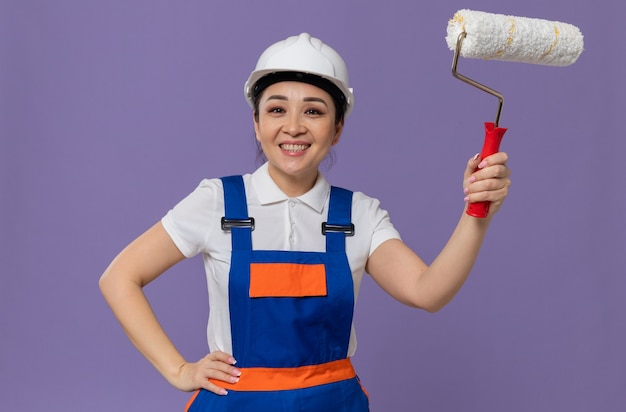 Glimlachend jong aziatisch bouwmeisje met witte veiligheidshelm die hand op haar taille legt en verfroller vasthoudt