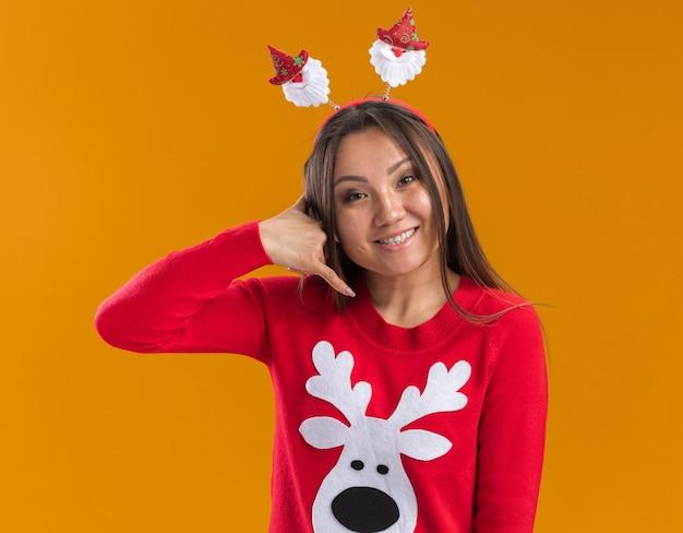 Glimlachend jong aziatisch meisje dat de hoepel van het kerstmishaar met sweater draagt die telefoongesprekgebaar toont dat op oranje muur wordt geïsoleerd