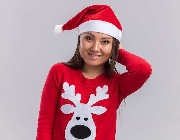 Glimlachend jong aziatisch meisje dat kerstmishoed met de hand van de sweaterholding achter hoofd draagt dat op witte achtergrond wordt geïsoleerd