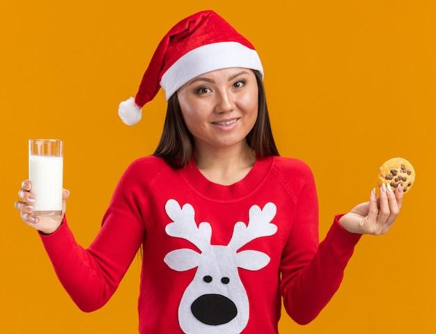 Glimlachend jong aziatisch meisje met kerstmuts met trui met glas melk met koekjes geïsoleerd op een oranje achtergrond