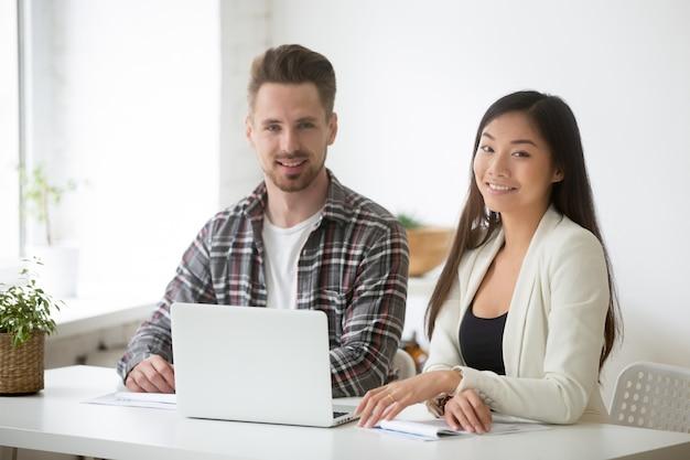 Glimlachend jong aziatisch onderneemster en zakenmankersteamportret