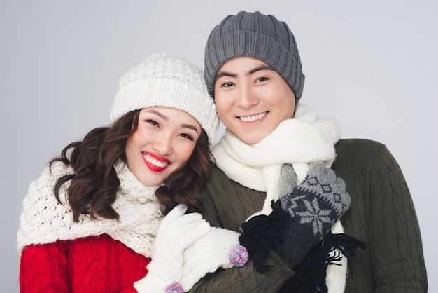 Glimlachend jong aziatisch paar dat gebreide warme sjaal draagt, over grijze achtergrond