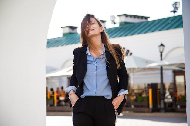 Glimlachend jong bedrijfsvrouwenportret in kostuum met mooi lang haar.