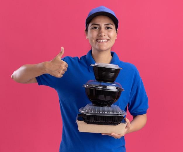 Glimlachend jong bezorgmeisje dat een uniform draagt met een pet die voedselcontainers vasthoudt met duim omhoog geïsoleerd op roze muur