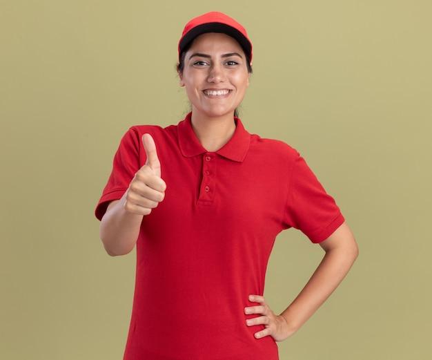 Glimlachend jong bezorgmeisje dat uniform draagt met een pet die duim omhoog laat zien en hand op de heup zet, geïsoleerd op olijfgroene muur