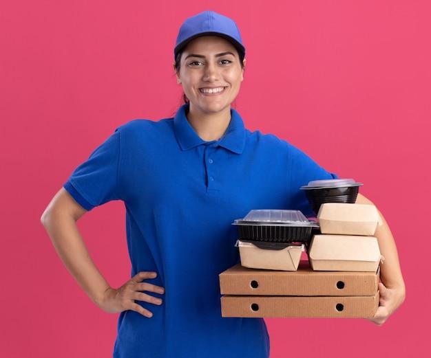 Glimlachend jong bezorgmeisje die uniform met pet dragen die voedselcontainers op pizzadozen houden die hand op heup zetten die op roze muur wordt geïsoleerd