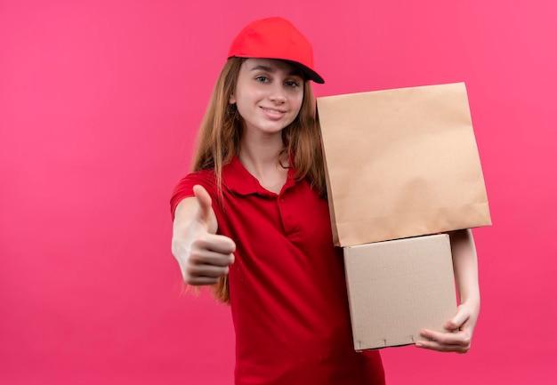 Glimlachend jong bezorgmeisje in rode uniforme holdingsdozen en duim opdagen op geïsoleerde roze ruimte met exemplaarruimte