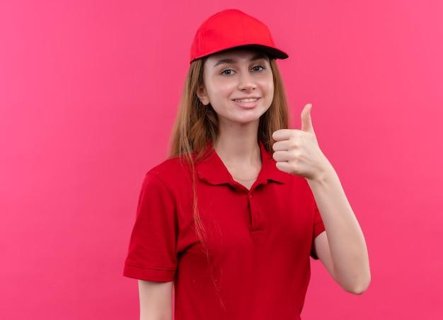 Glimlachend jong bezorgmeisje in rood uniform die duim op geïsoleerde roze muur met exemplaarruimte toont