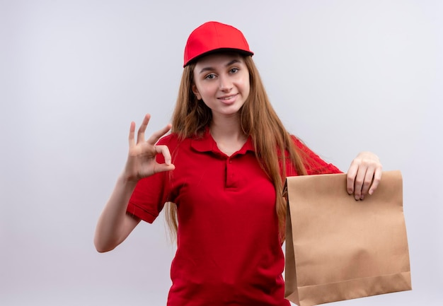 Glimlachend jong bezorgmeisje in rood uniform doet ok teken en houdt papieren zak op geïsoleerde witte ruimte