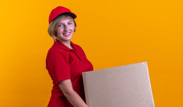 Glimlachend jong bezorgmeisje in uniform met dop met doos geïsoleerd op een oranje muur