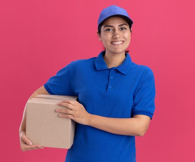 Glimlachend jong bezorgmeisje in uniform met dop met doos geïsoleerd op roze muur