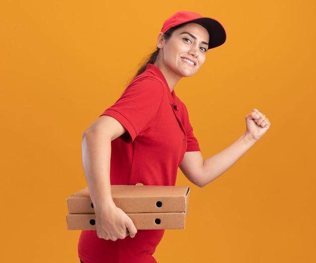Glimlachend jong bezorgmeisje met uniform en pet met pizzadozen met een rennend gebaar geïsoleerd op een oranje muur
