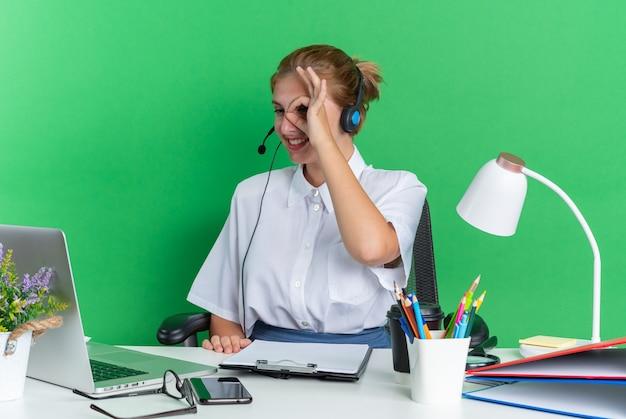 Glimlachend jong blond callcentermeisje met een hoofdtelefoon die aan een bureau zit met uitrustingsstukken die naar een laptop kijken en een gebaar maken