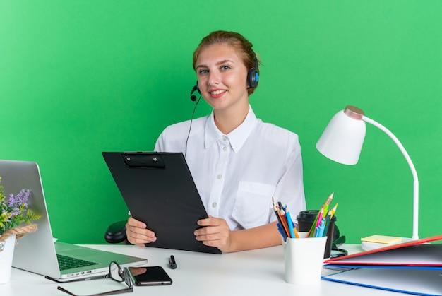 Glimlachend jong blond callcentermeisje met hoofdtelefoon zittend aan een bureau met uitrustingsstukken met klembord kijkend naar camera geïsoleerd op groene muur