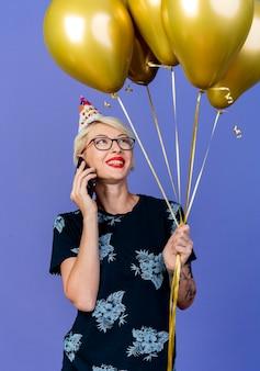 Glimlachend jong blond feestmeisje met bril en verjaardag glb houden en kijken naar ballonnen praten over telefoon geïsoleerd op paarse achtergrond