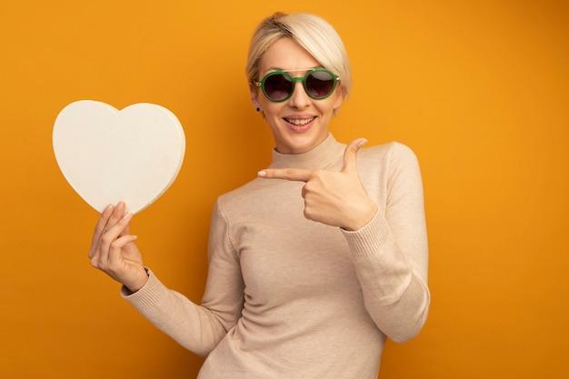 Glimlachend jong blond meisje met een zonnebril die vasthoudt en wijst naar hartvorm geïsoleerd op een oranje muur