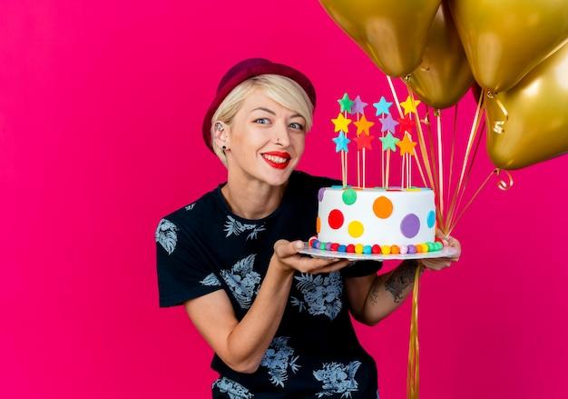Glimlachend jong blond partijmeisje die partijhoed dragen die ballons en verjaardagstaart met sterren bekijken die camera bekijken die op karmozijnrode achtergrond met exemplaarruimte wordt geïsoleerd