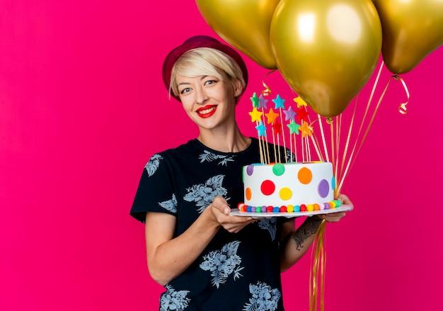 Glimlachend jong blond partijmeisje die partijhoed dragen die ballons en verjaardagstaart met sterren bekijken die camera bekijken die op karmozijnrode achtergrond wordt geïsoleerd