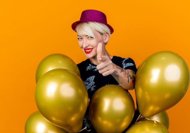 Glimlachend jong blond partijmeisje die partijhoed dragen die zich achter ballons bevinden die en op camera kijken die op oranje achtergrond wordt geïsoleerd
