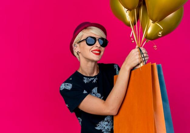 Glimlachend jong blond partijmeisje die partijhoed en zonnebril dragen die ballons en papieren zakken houden die camera bekijken die op karmozijnrode achtergrond met exemplaarruimte wordt geïsoleerd
