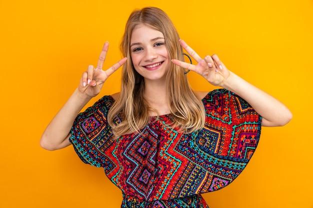 Glimlachend jong blond slavisch meisje dat overwinningsteken gebaart