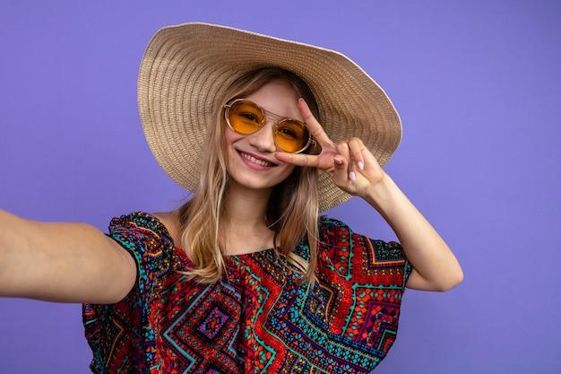 Glimlachend jong blond slavisch meisje met zonnebril en met zonnehoed gebarend overwinningsteken en