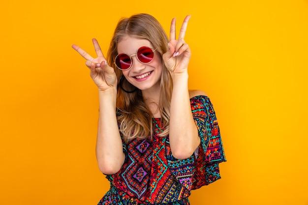 Glimlachend jong blond slavisch meisje met zonnebril gebarend overwinningsteken