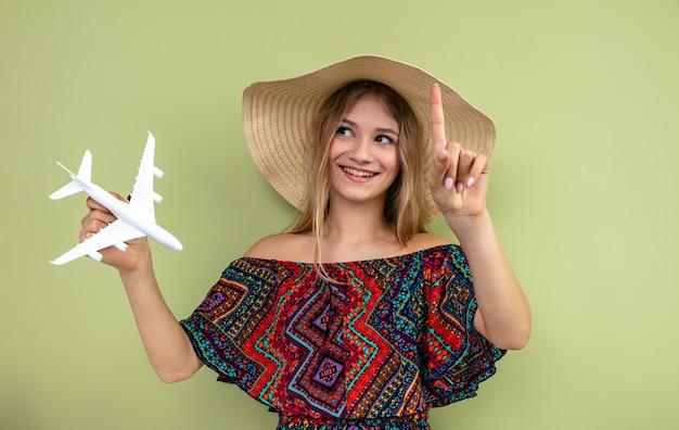 Glimlachend jong blond slavisch meisje met zonnehoed die vliegtuigmodel vasthoudt en omhoog wijst