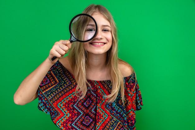 Glimlachend jong blond slavisch meisje vasthouden en door vergrootglas Gratis Foto
