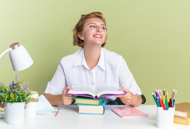 Glimlachend jong blond studentenmeisje dat aan een bureau zit met schoolhulpmiddelen die een open boek houden en naar de zijkant kijken
