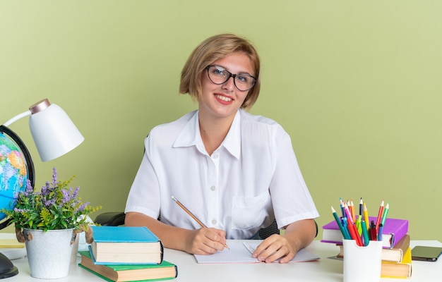Glimlachend jong blond studentenmeisje met een bril die aan een bureau zit met schoolhulpmiddelen die naar een camera kijken die een potlood vasthoudt op een olijfgroene muur