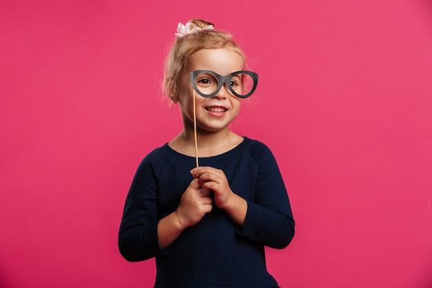 Glimlachend jong blondemeisje gebruikend document oogglazen en bekijkend de camera over roze muur