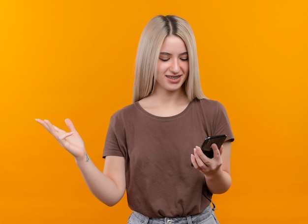Glimlachend jong blondemeisje in tandsteunen die mobiele telefoon houden die het bekijken met lege hand op geïsoleerde oranje ruimte met exemplaarruimte tonen