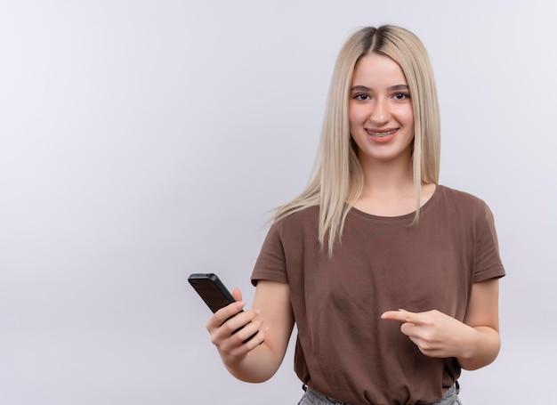 Glimlachend jong blondemeisje in tandsteunen die mobiele telefoon houden en op geïsoleerde witte ruimte met exemplaarruimte richten