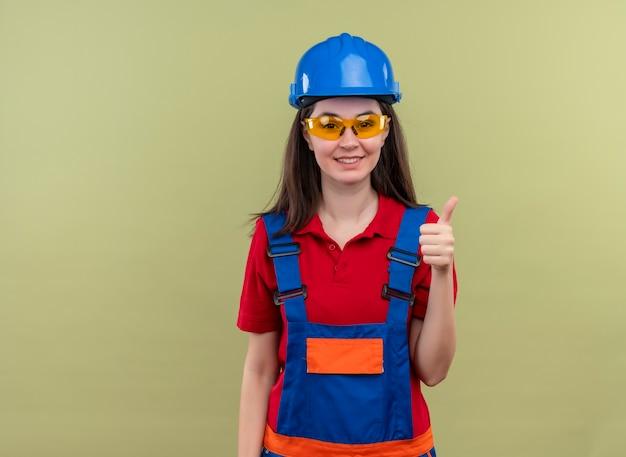 Glimlachend jong bouwersmeisje met blauwe veiligheidshelm en met veiligheidsbril beduimelt omhoog op geïsoleerde groene achtergrond met exemplaarruimte