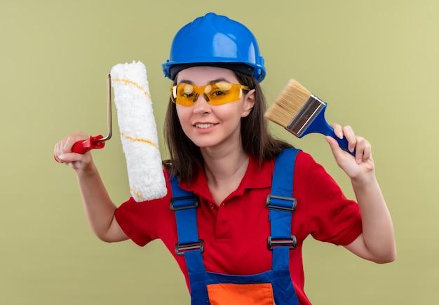 Glimlachend jong bouwersmeisje met blauwe veiligheidshelm en met veiligheidsbril houdt verfroller en kwast op geïsoleerde groene achtergrond